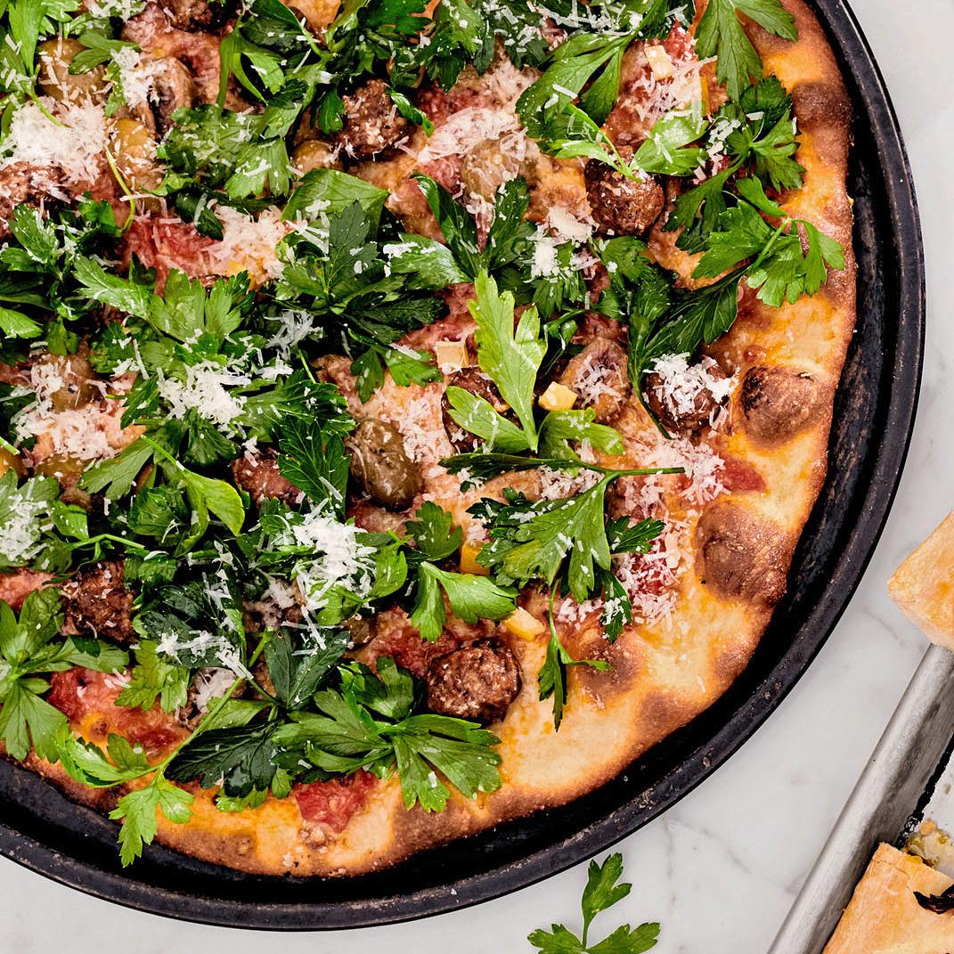 merguez pizza with olives parsley salad