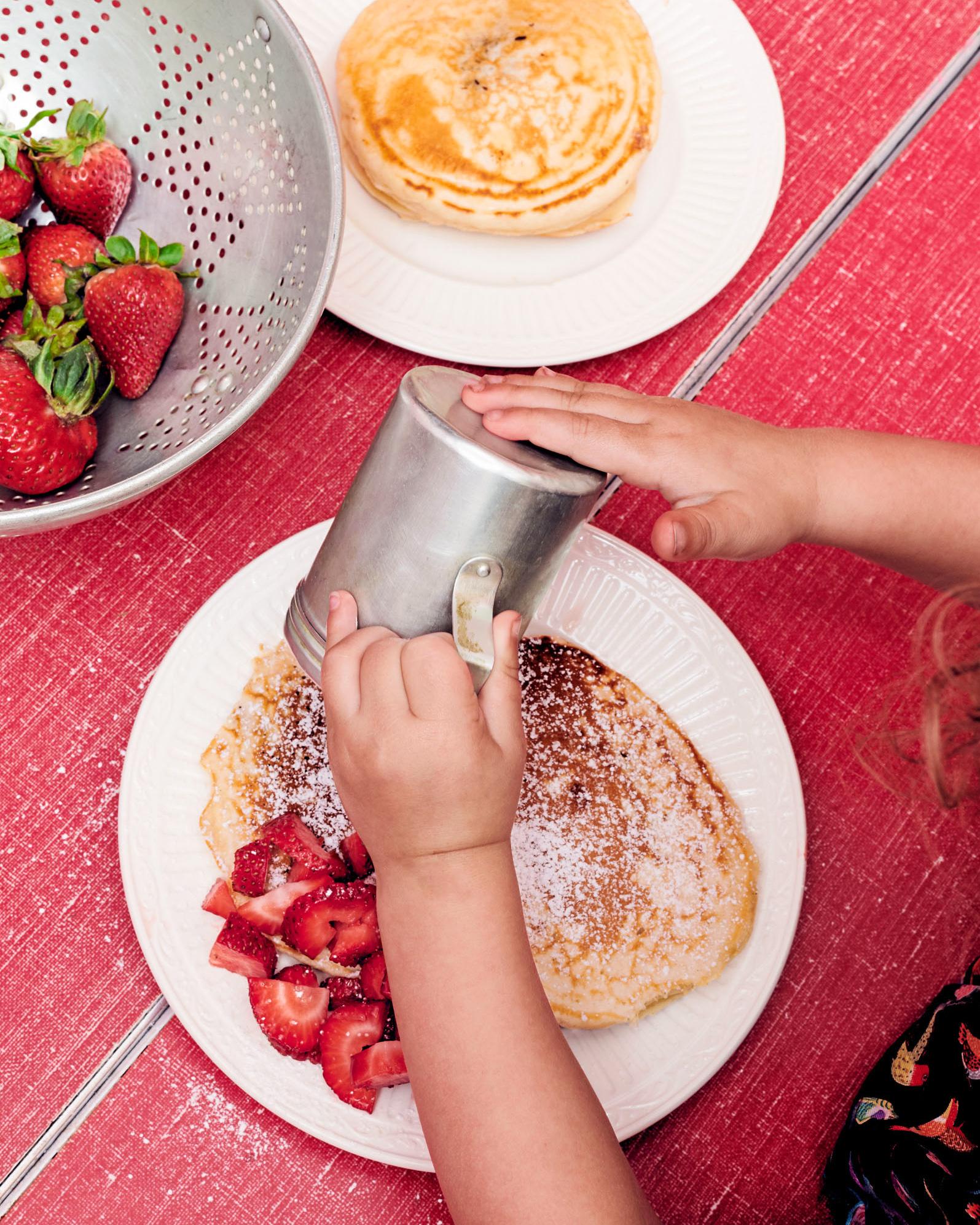 sprinkling sugar on chocolate hazelnut pancakes