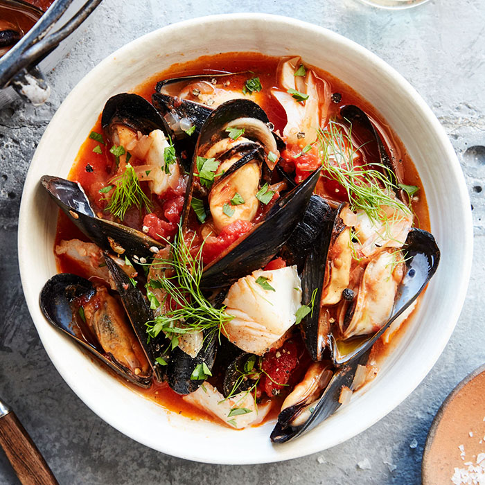 seafood and fennel cioppino in white bowl