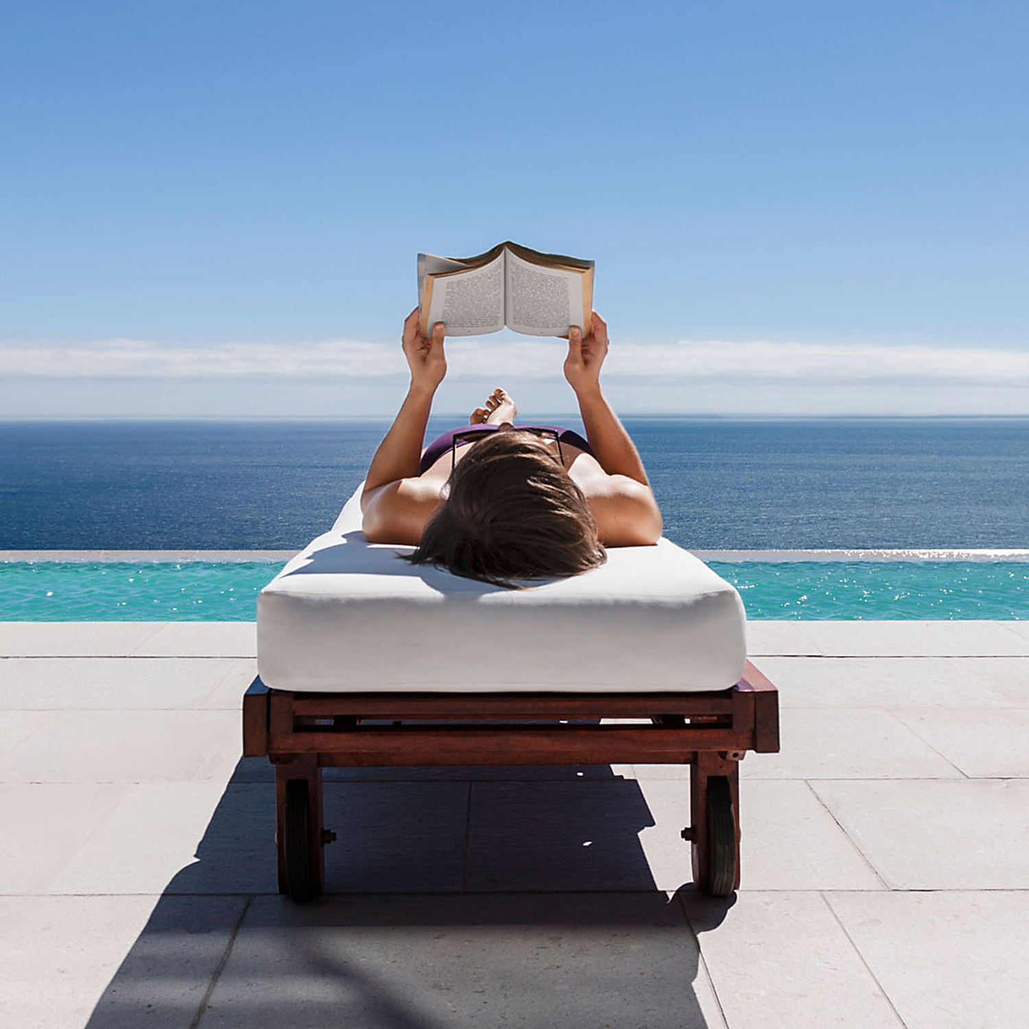 woman reading on lounge chair ocean view