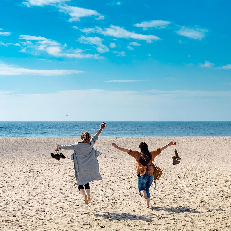 two women running joyfully on beach