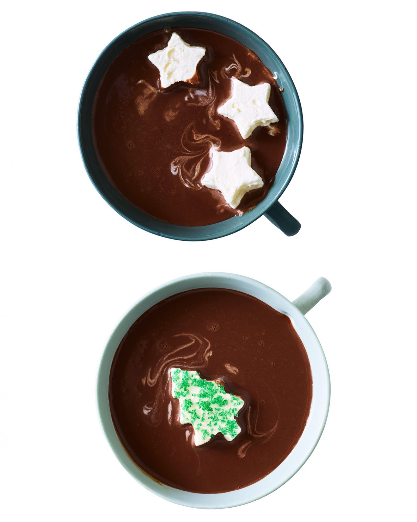 two mugs of hot cocoa with festive whipped cream shapes