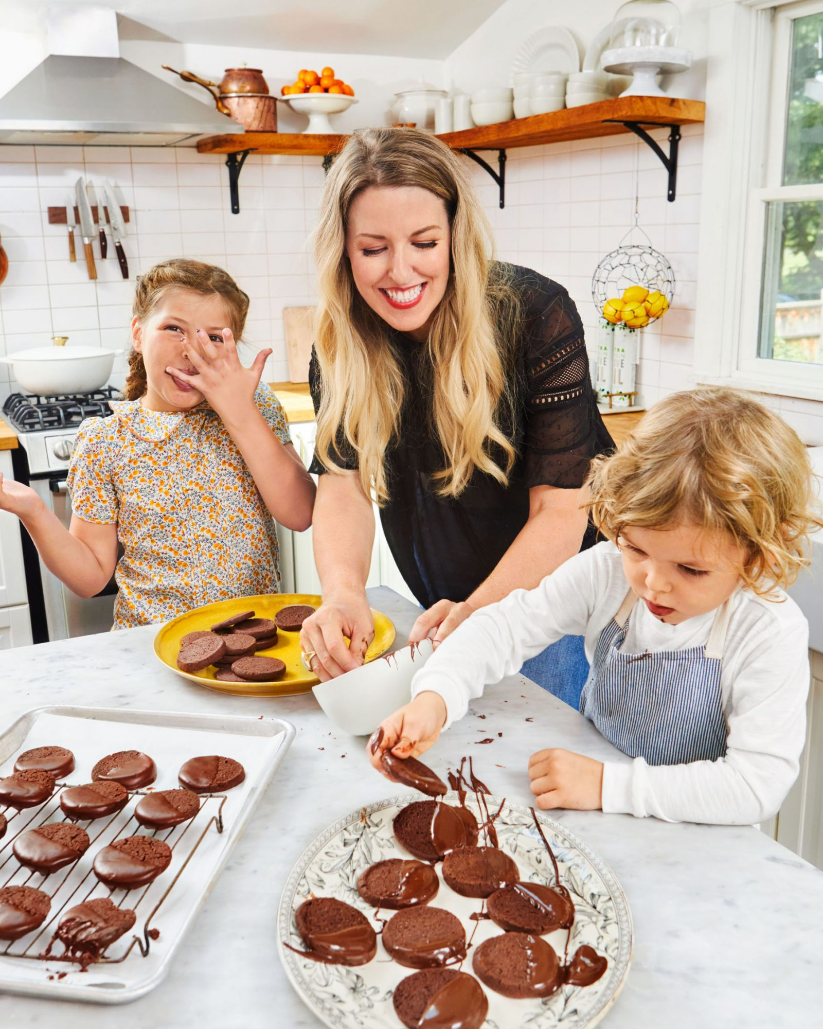 mom and kids dipping chocolate cookies