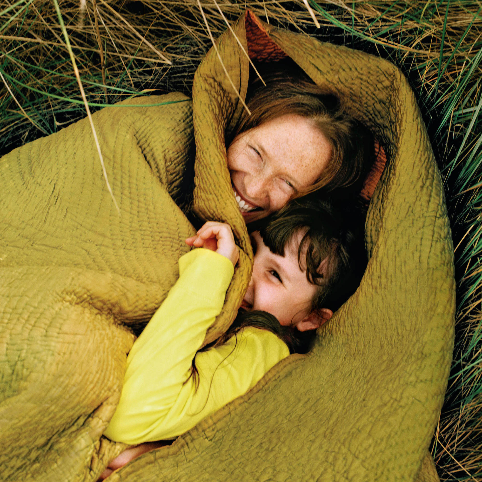 smiling mom and kid snuggling in blanket