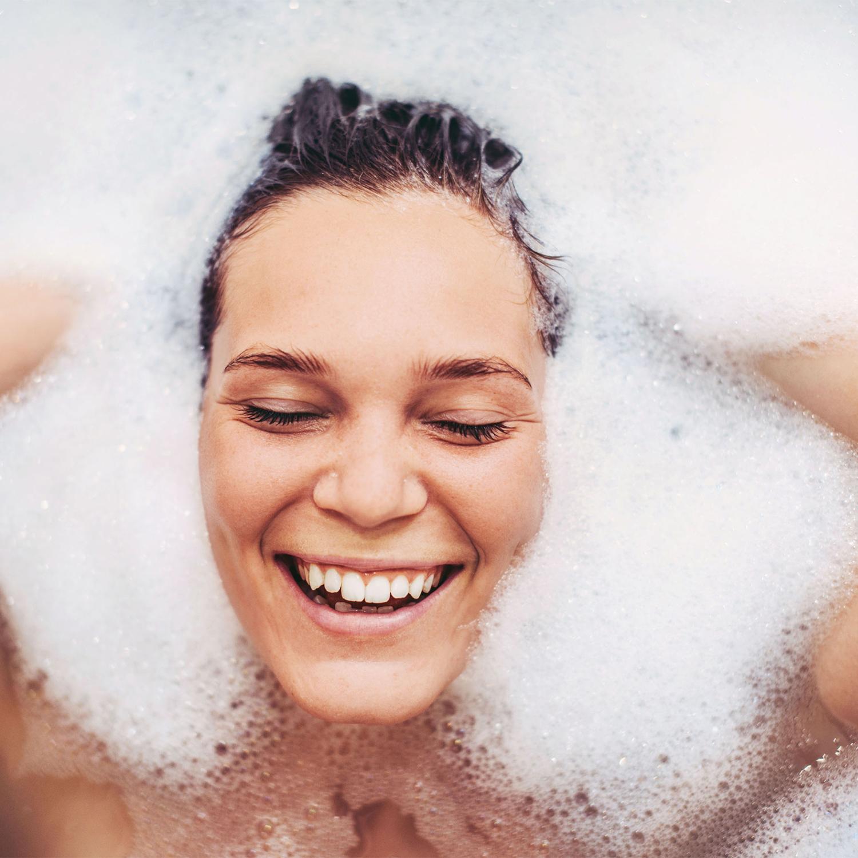 headshot happy woman submerged in bubble bath