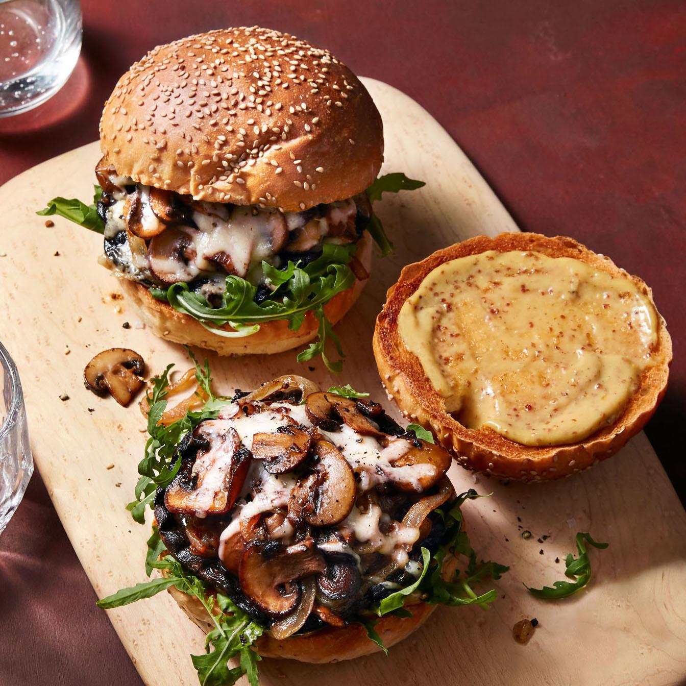 double mushroom cheeseburgers with arugula on cutting board