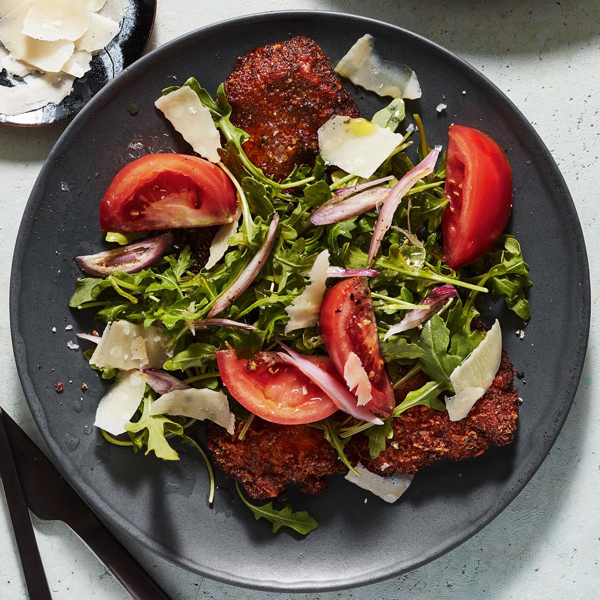 steak tomatoes arugula parmesan on black plate