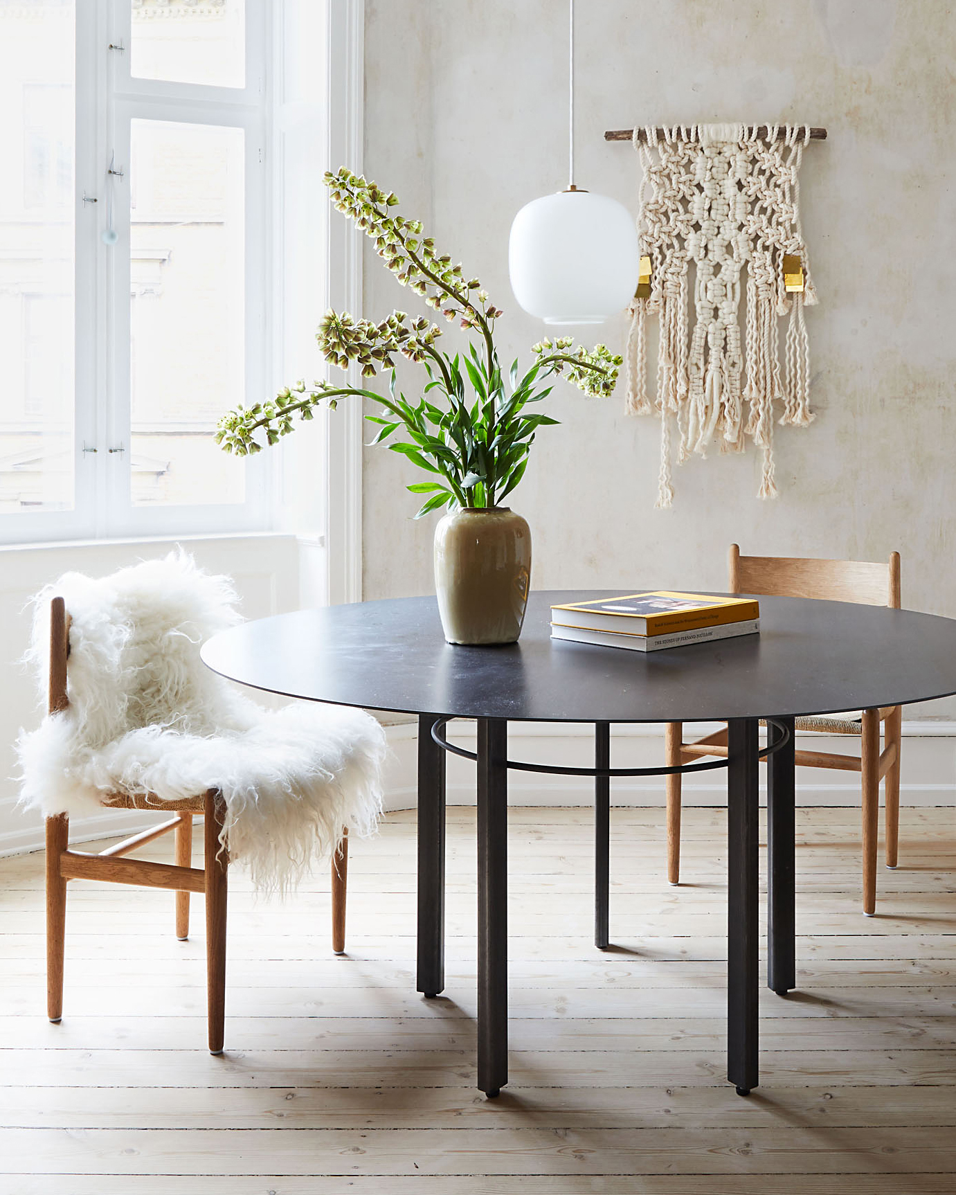 round table and chairs by window and wall hanging