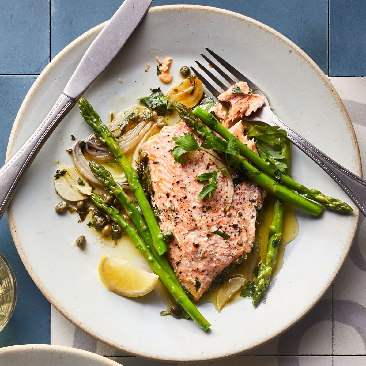arctic char with asparagus parsley and capers served on white plate
