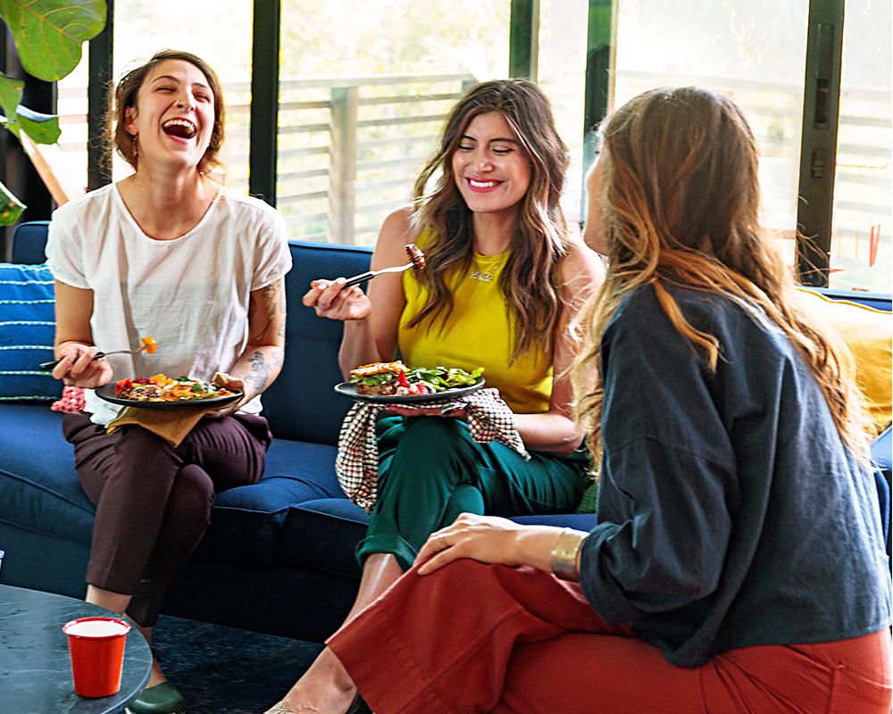 three women conversing in living room