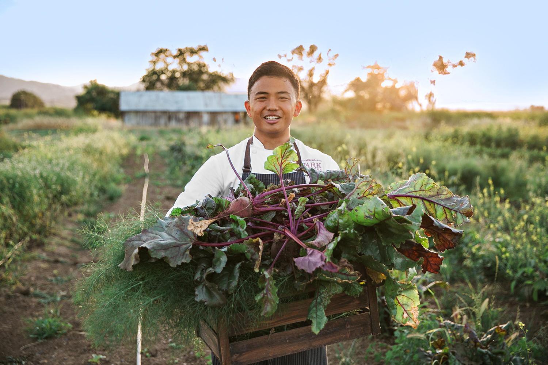 man holding large box of freshly cut produce