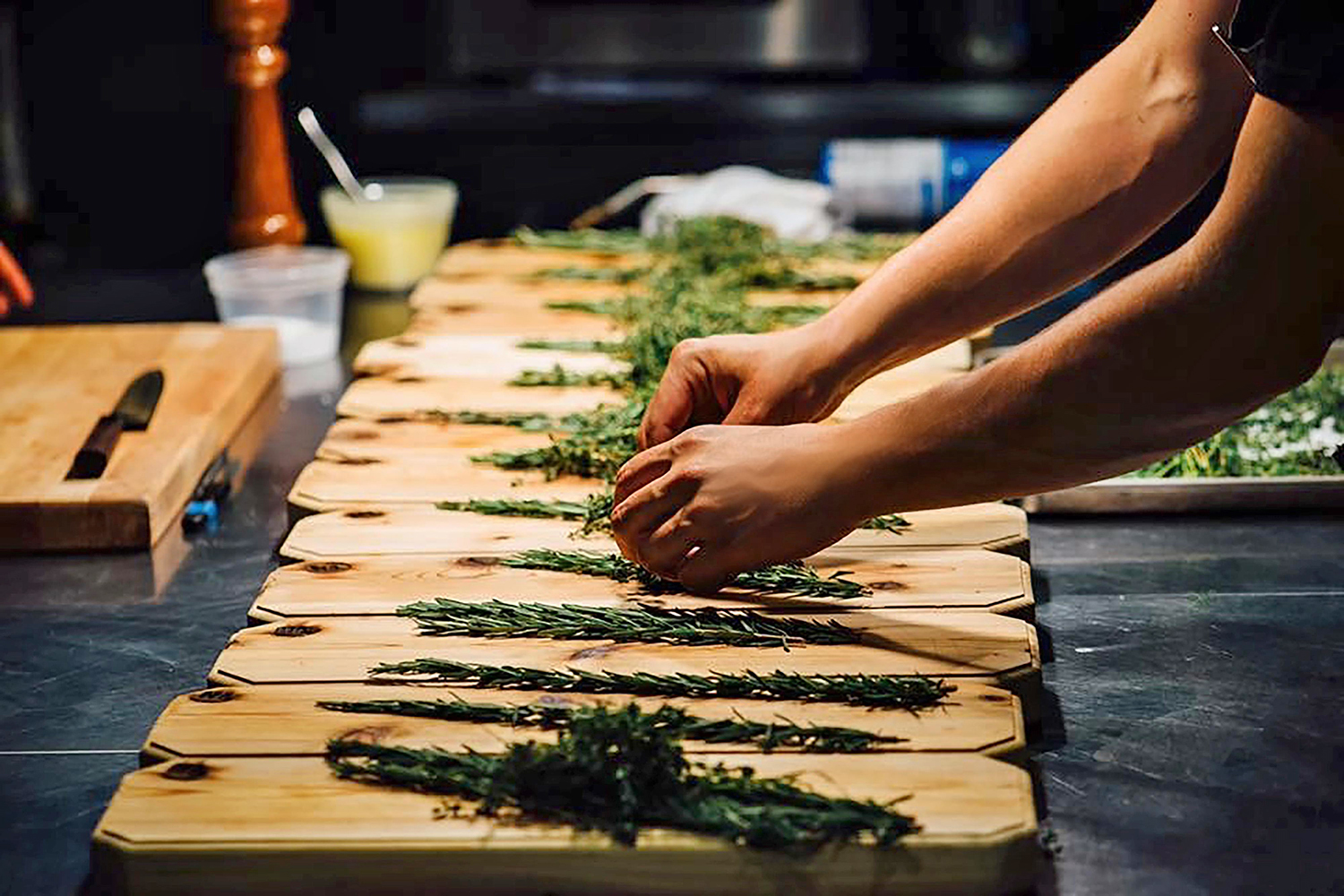 person placing rosemary on wooden slabs