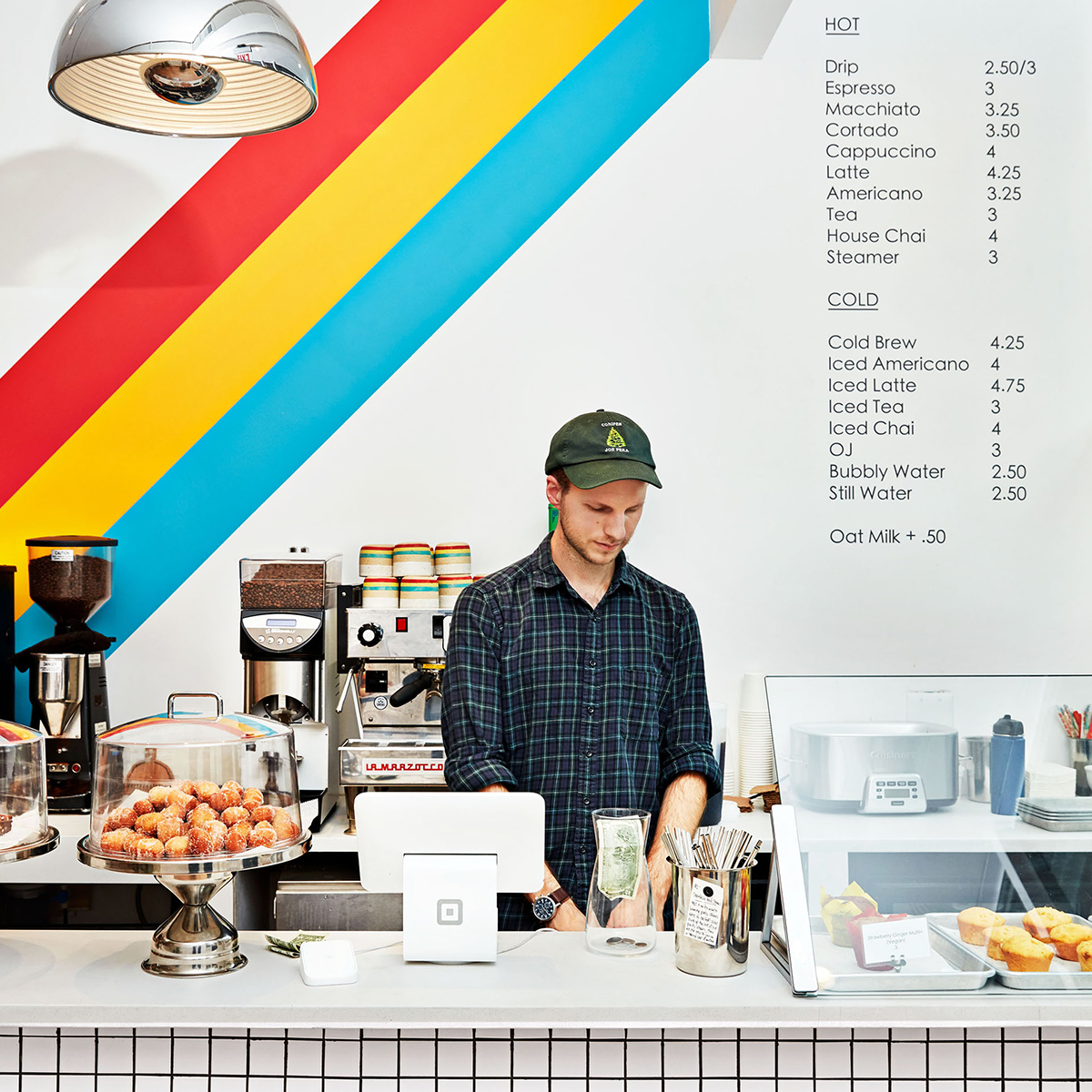 man in cafe serving coffee and pastries