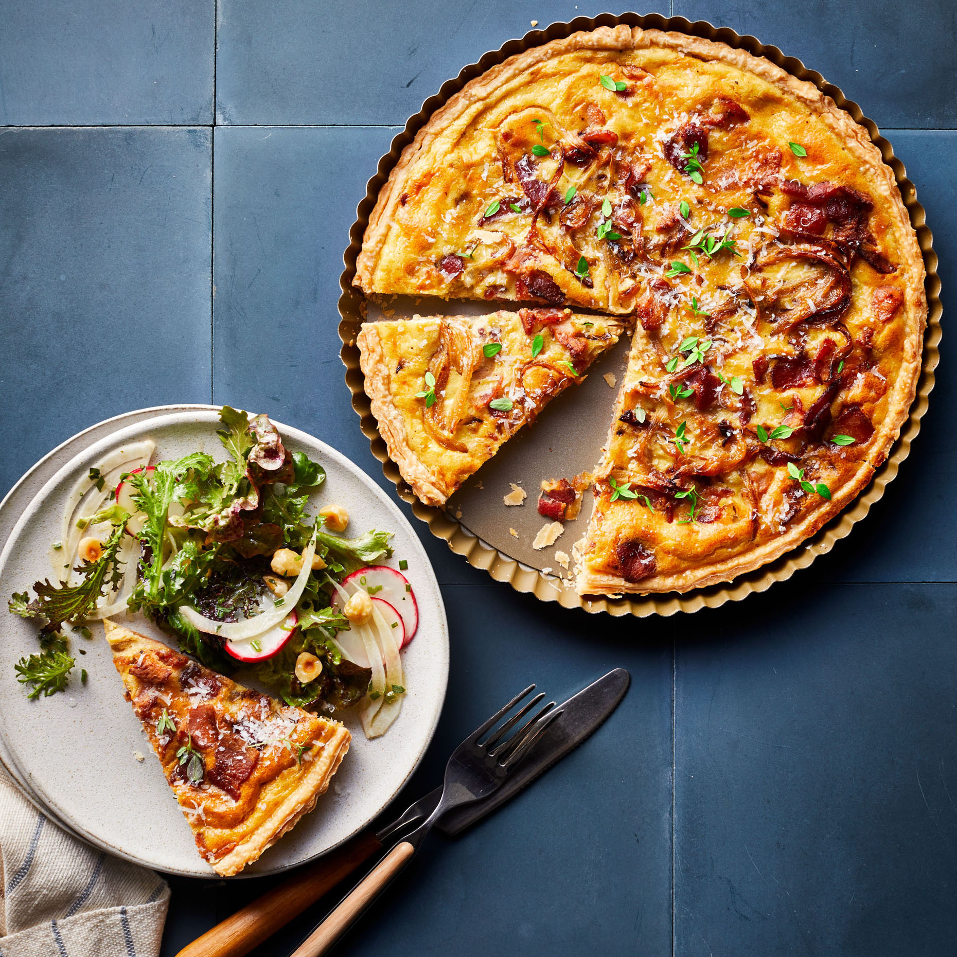 onion tart with bacon and mustard served with mixed greens