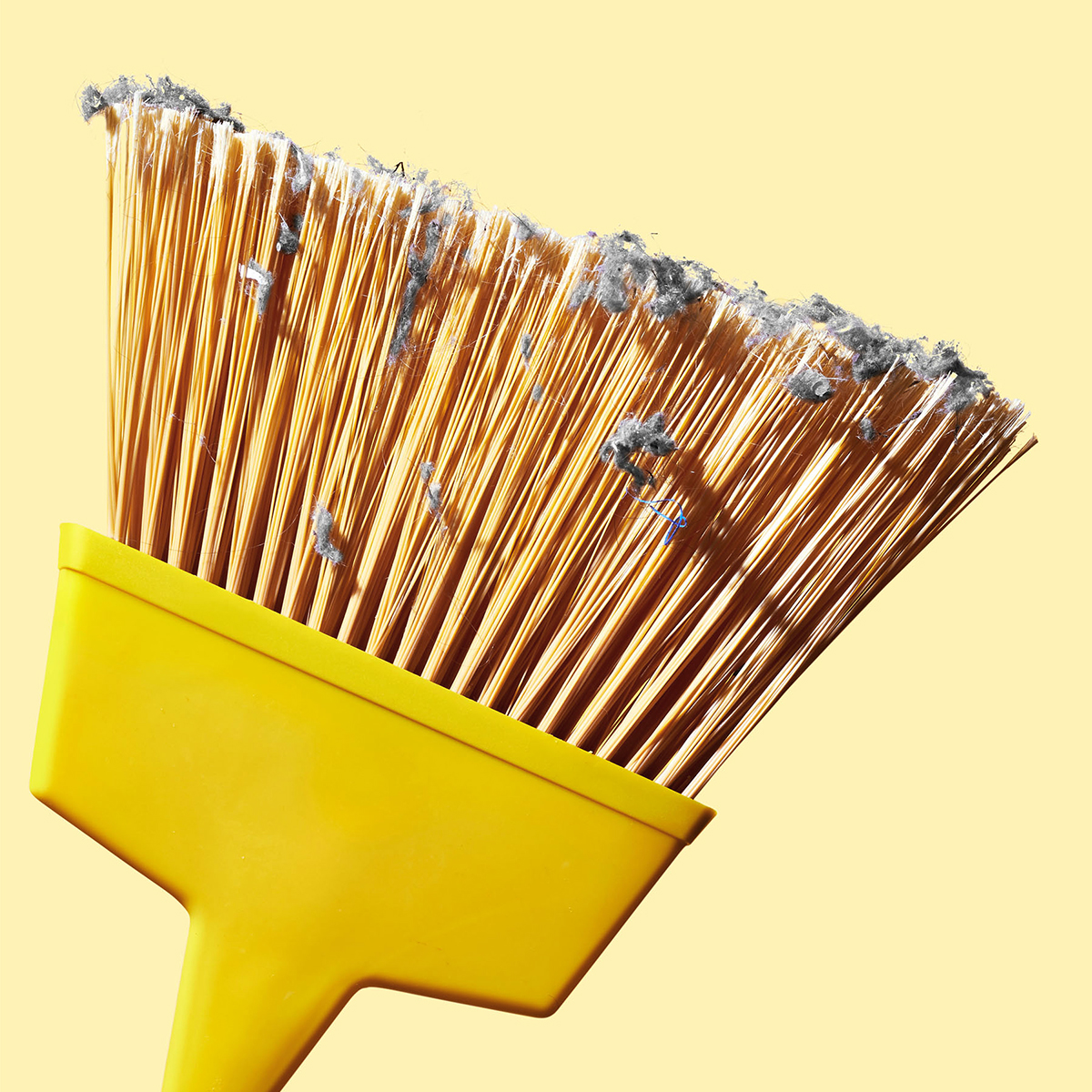yellow broom with dust