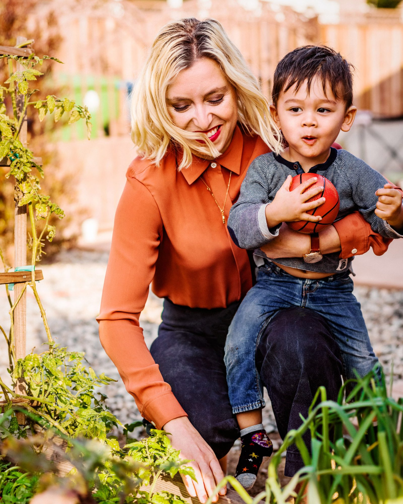 mother and son picking herbs in the garden