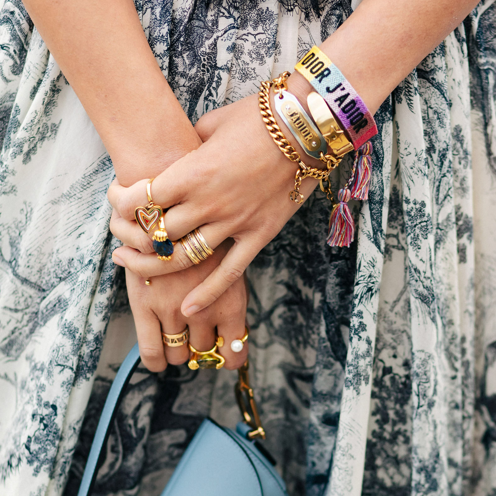 woman holding blue purse wearing bracelets and rings
