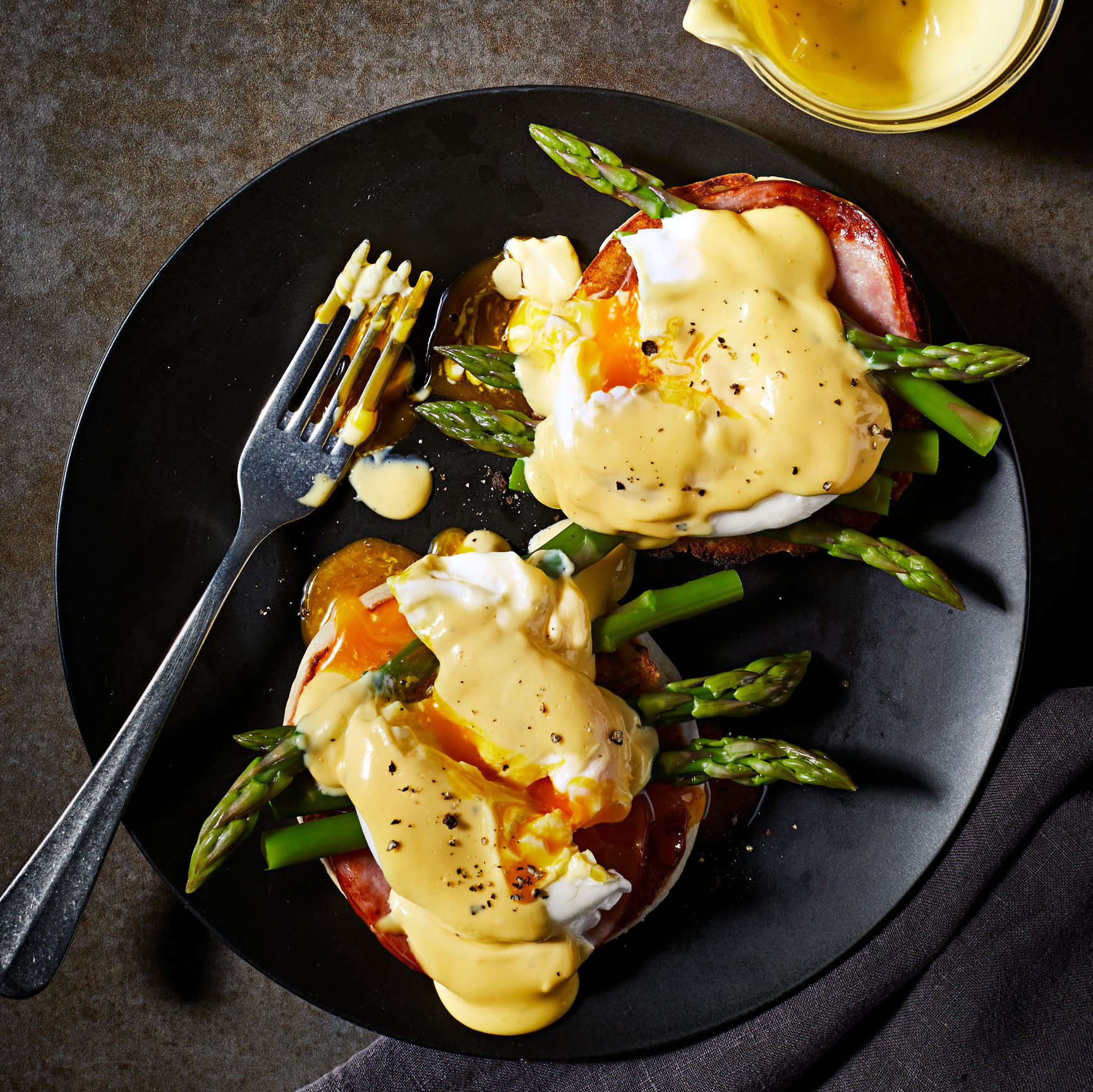 eggs benedict on a plate with asparagus