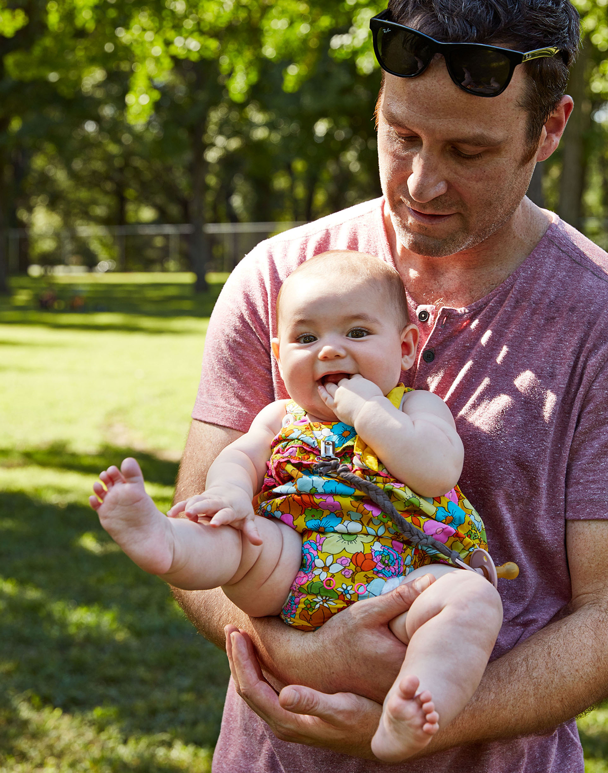 dad holding baby wearing floral print outfit outside
