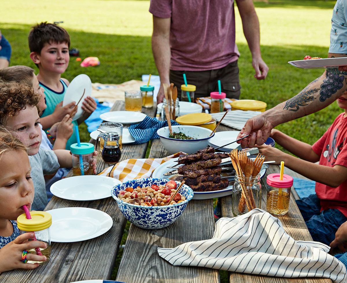 family sitting at wooden picnic table eating