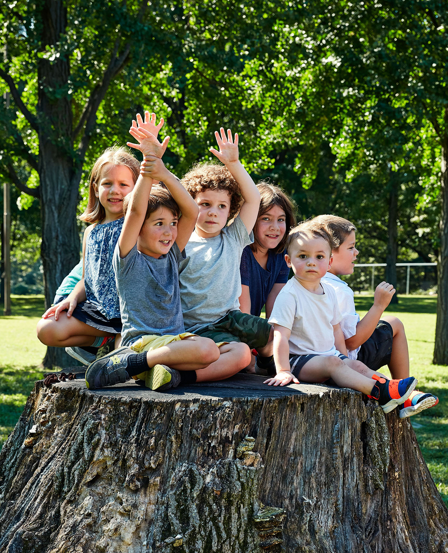 group of kids sitting on tree stump