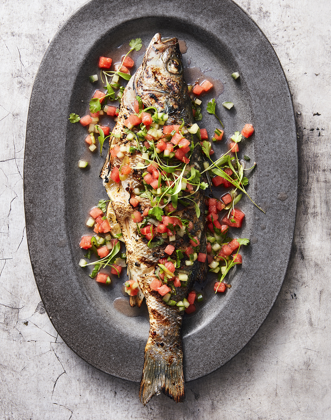 whole grilled fish with sauce and salsa