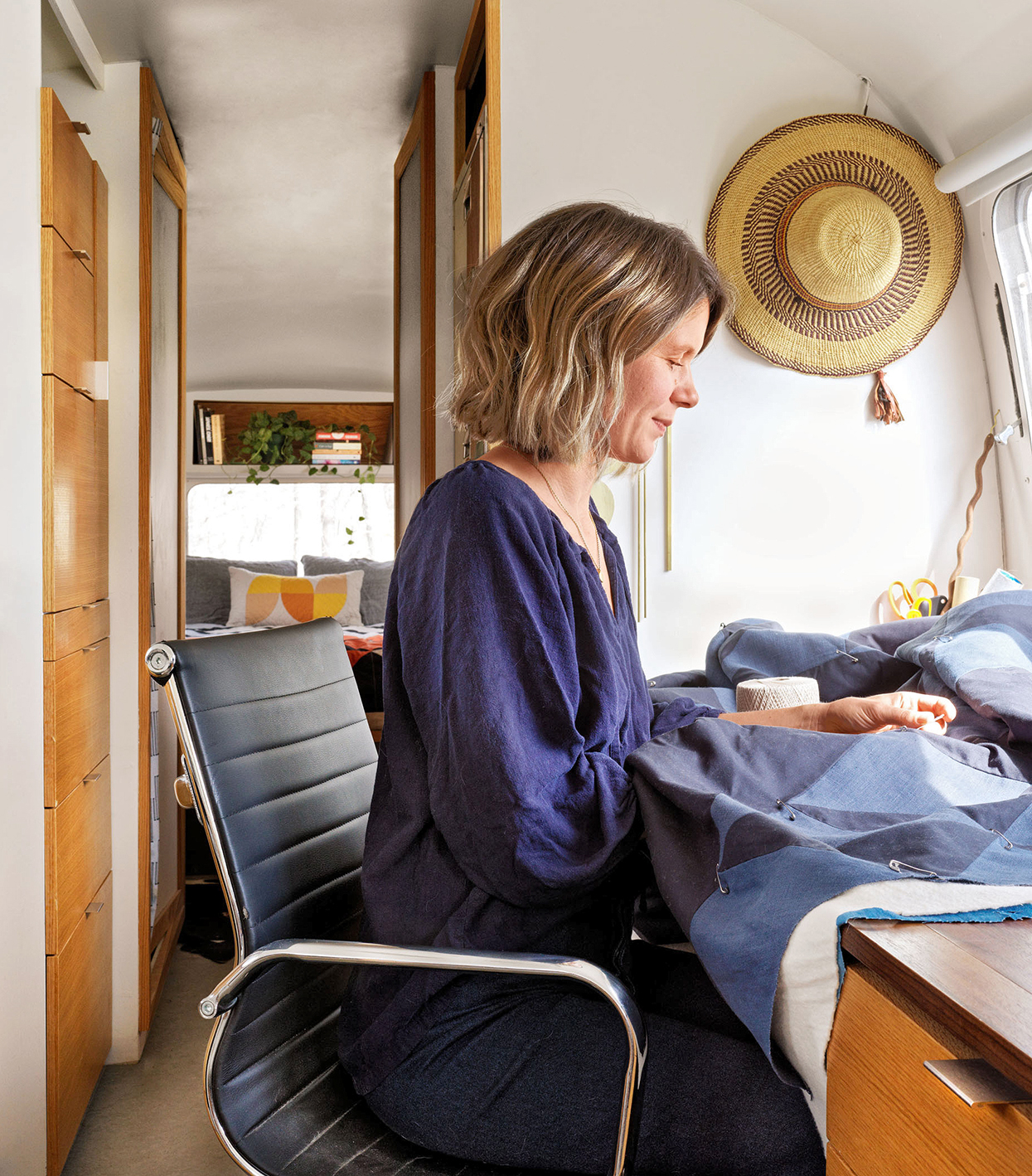 woman works on quilt in airstream trailer