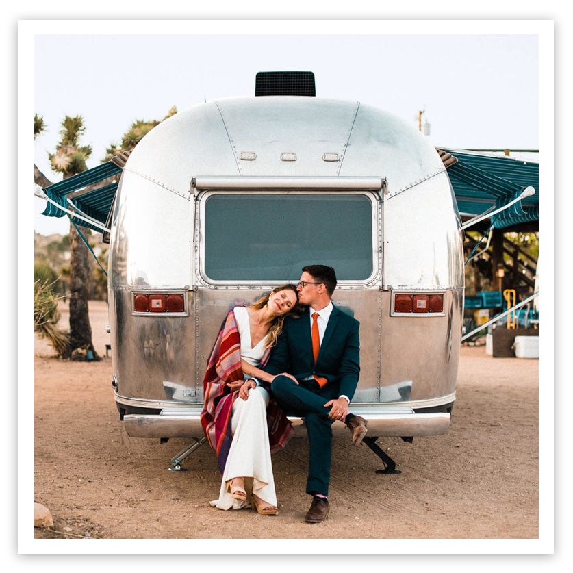 newlyweds sitting on airstream trailer