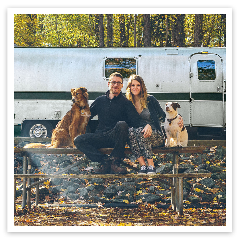 young couple with dogs near airstream