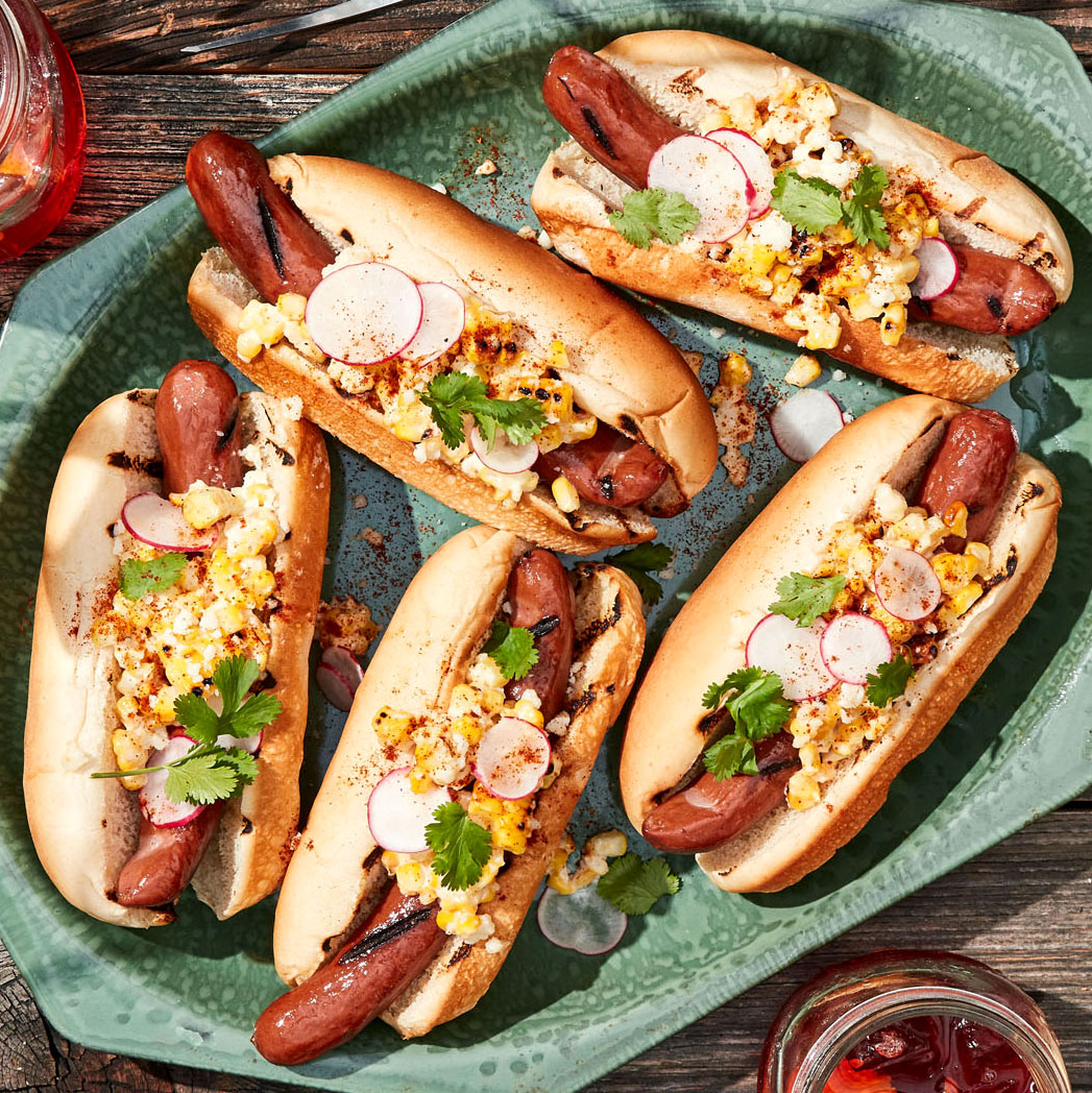 elote dogs topped with corn and radishes