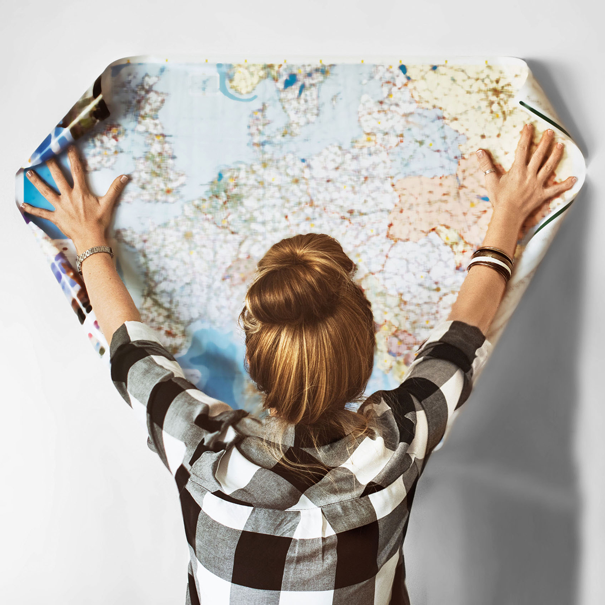 girl holding map to wall