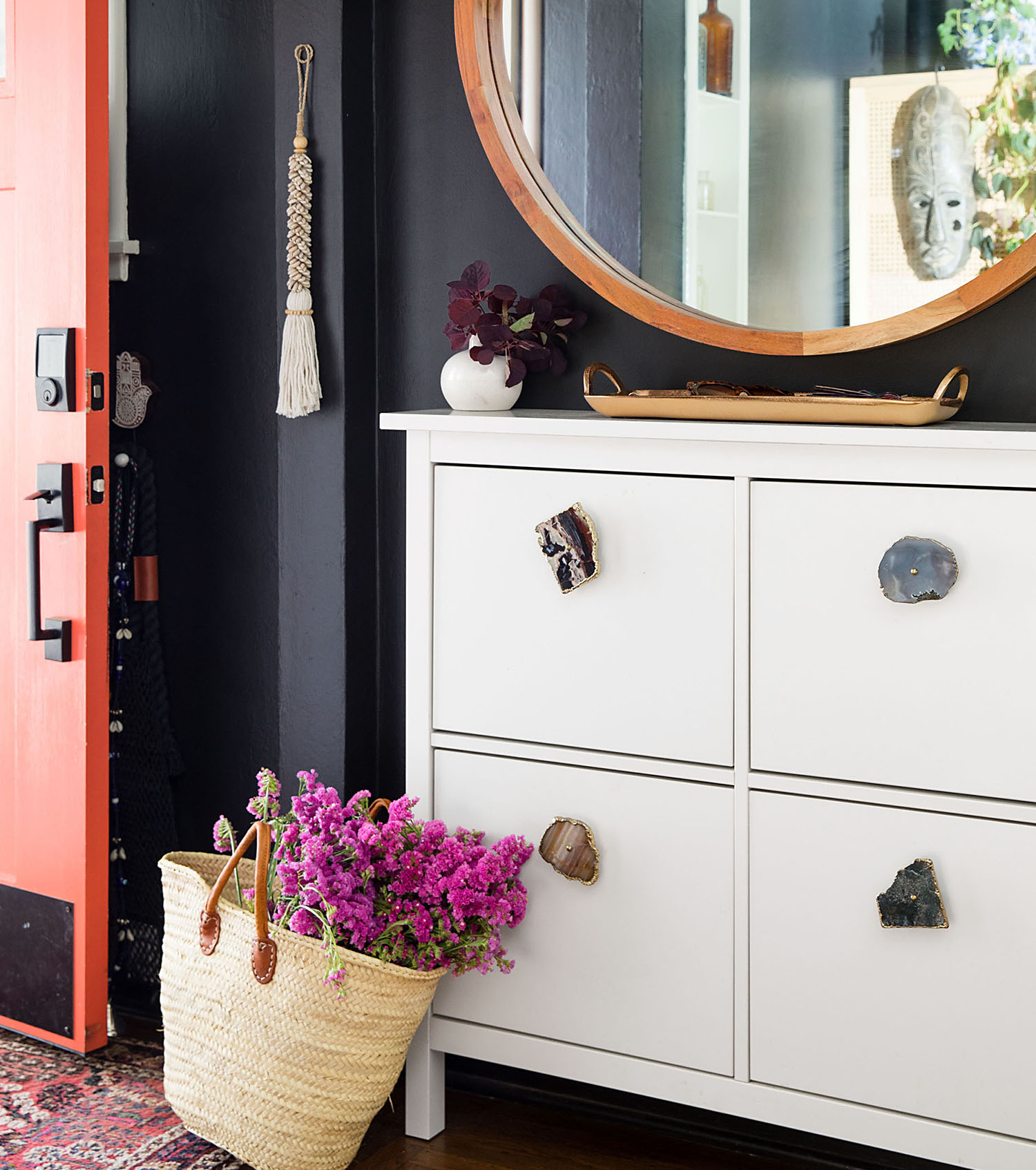 entry way with white drawers round mirror