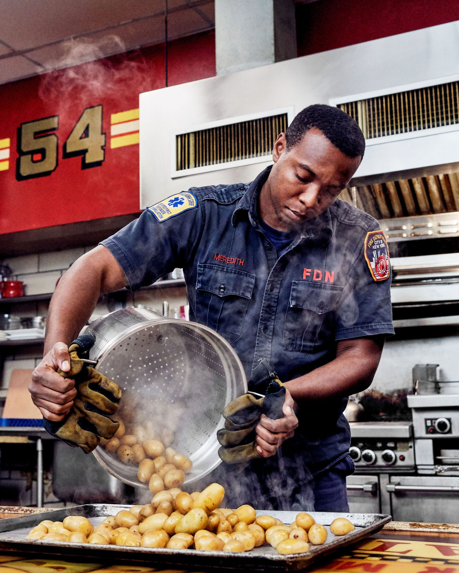 firefighter dumping baby potatoes onto tray