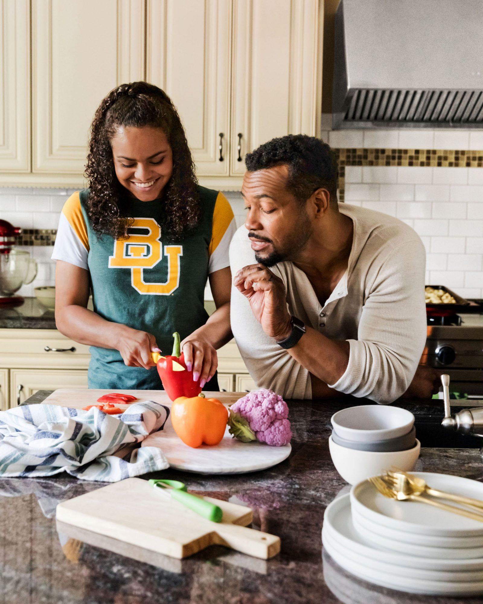 Isaiah Mustafa and daughter preparing vegetables
