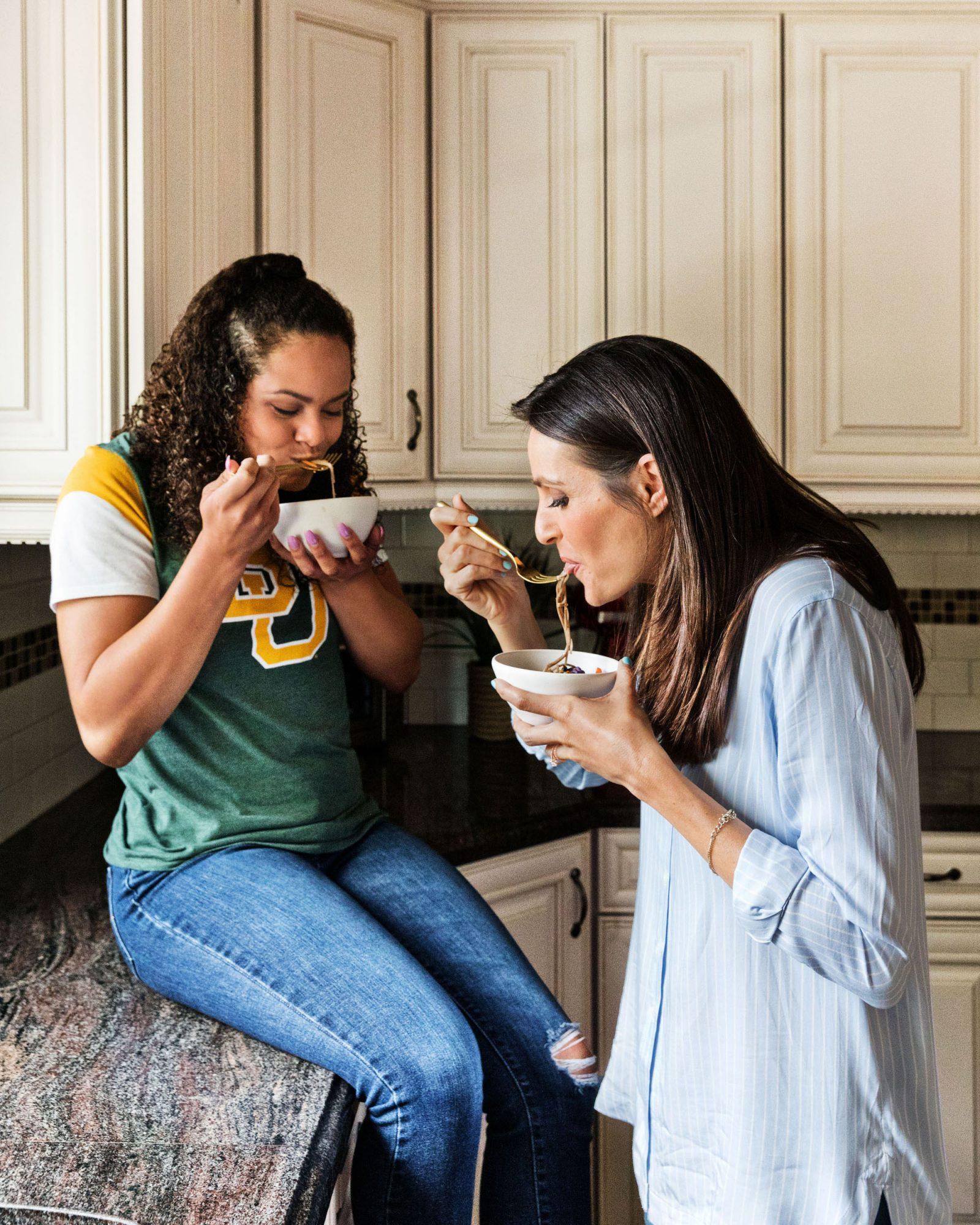 mother and daughter enjoy veggie noodle bowls