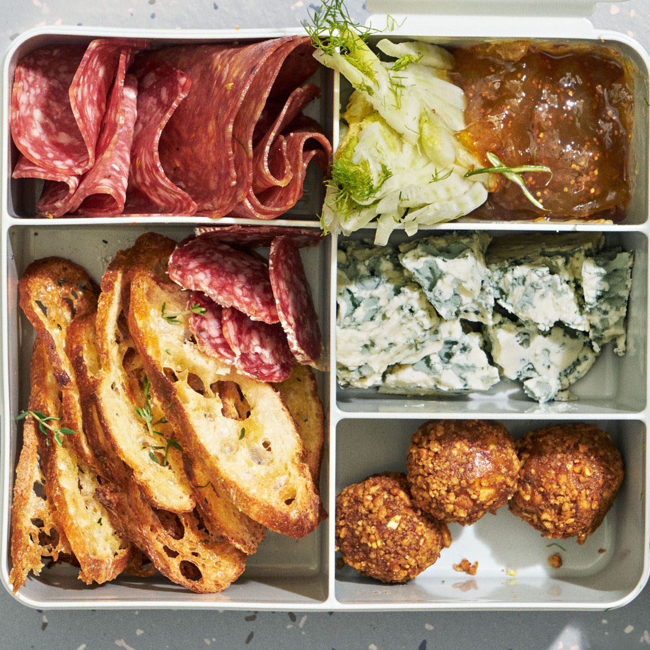 toast meats and cheeses served in a bento box