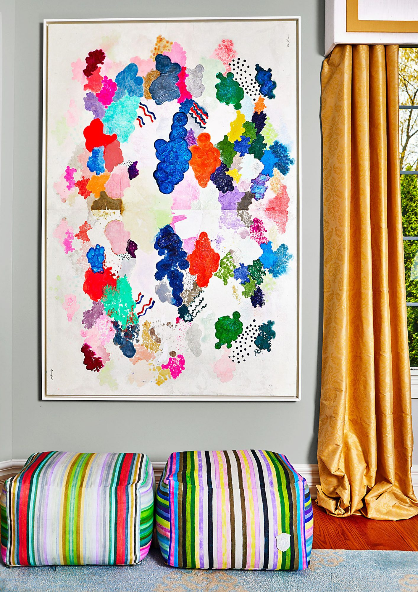 Kristi Kohut's framed artwork and colorful poufs