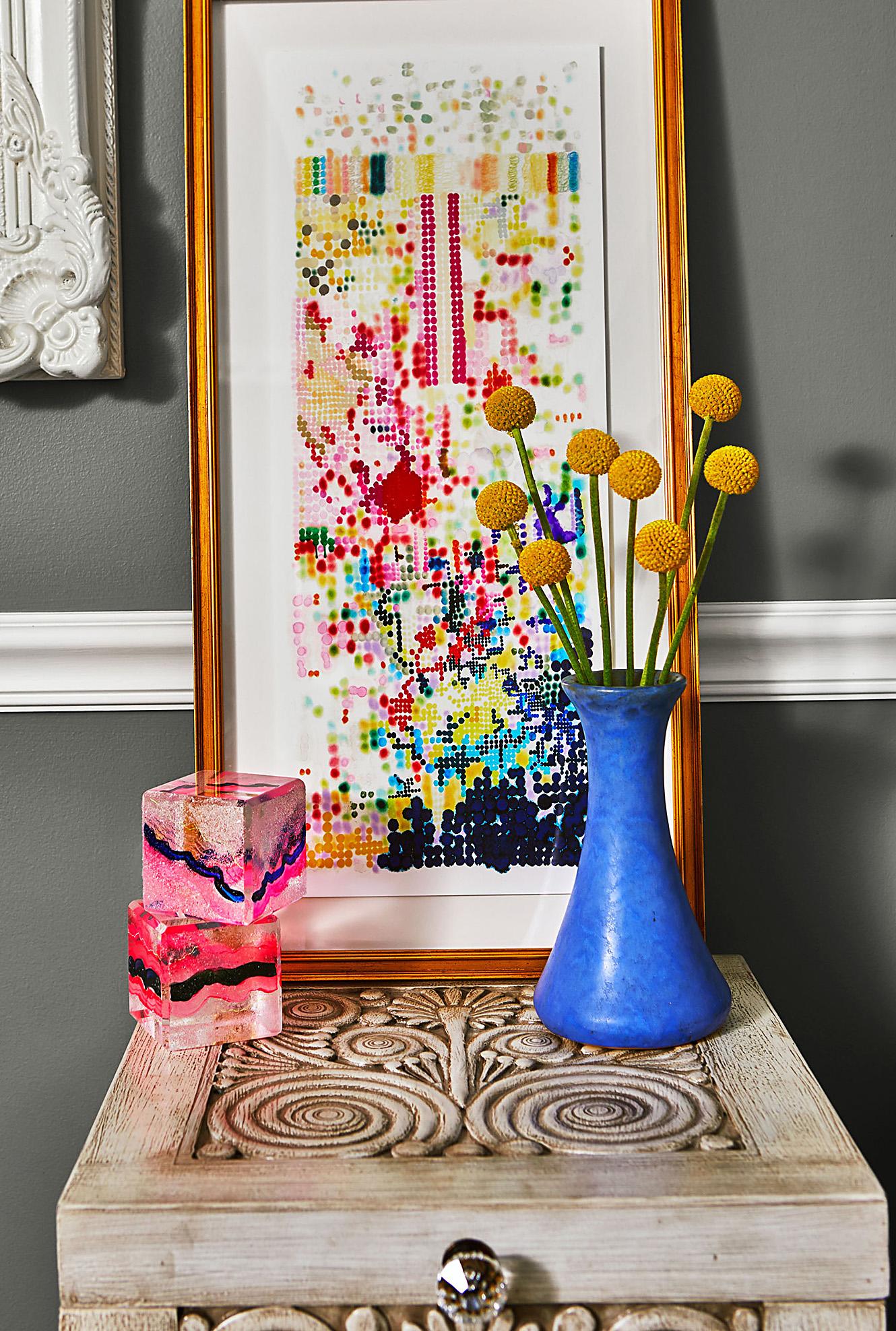 table with framed artwork sculpture cubes vase