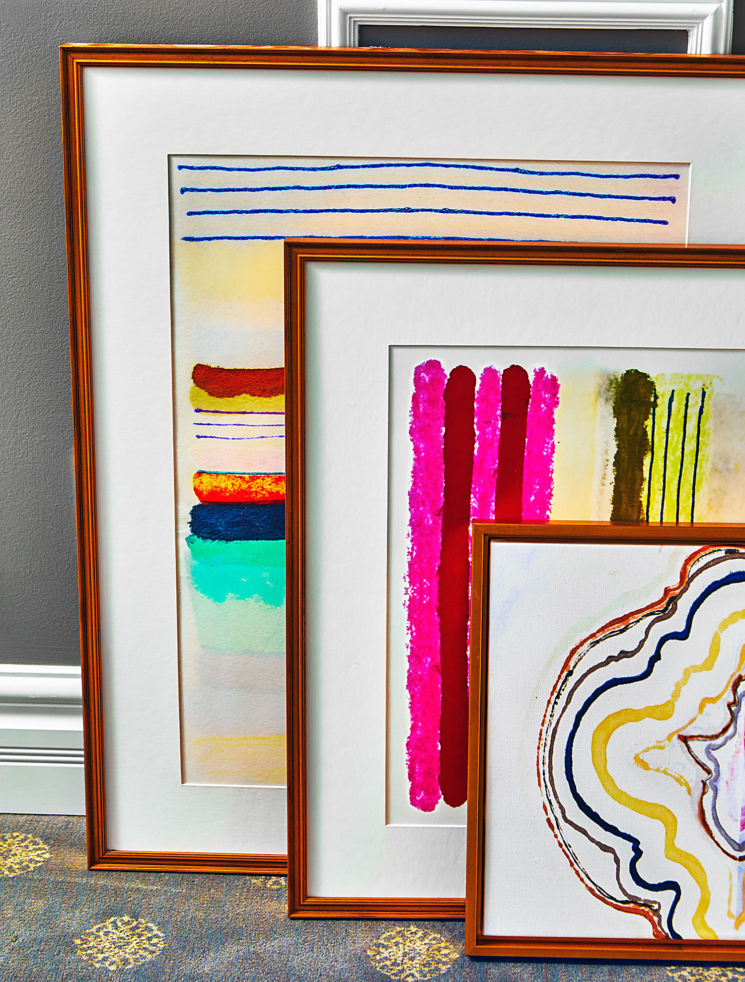 three pieces of framed artwork against office wall