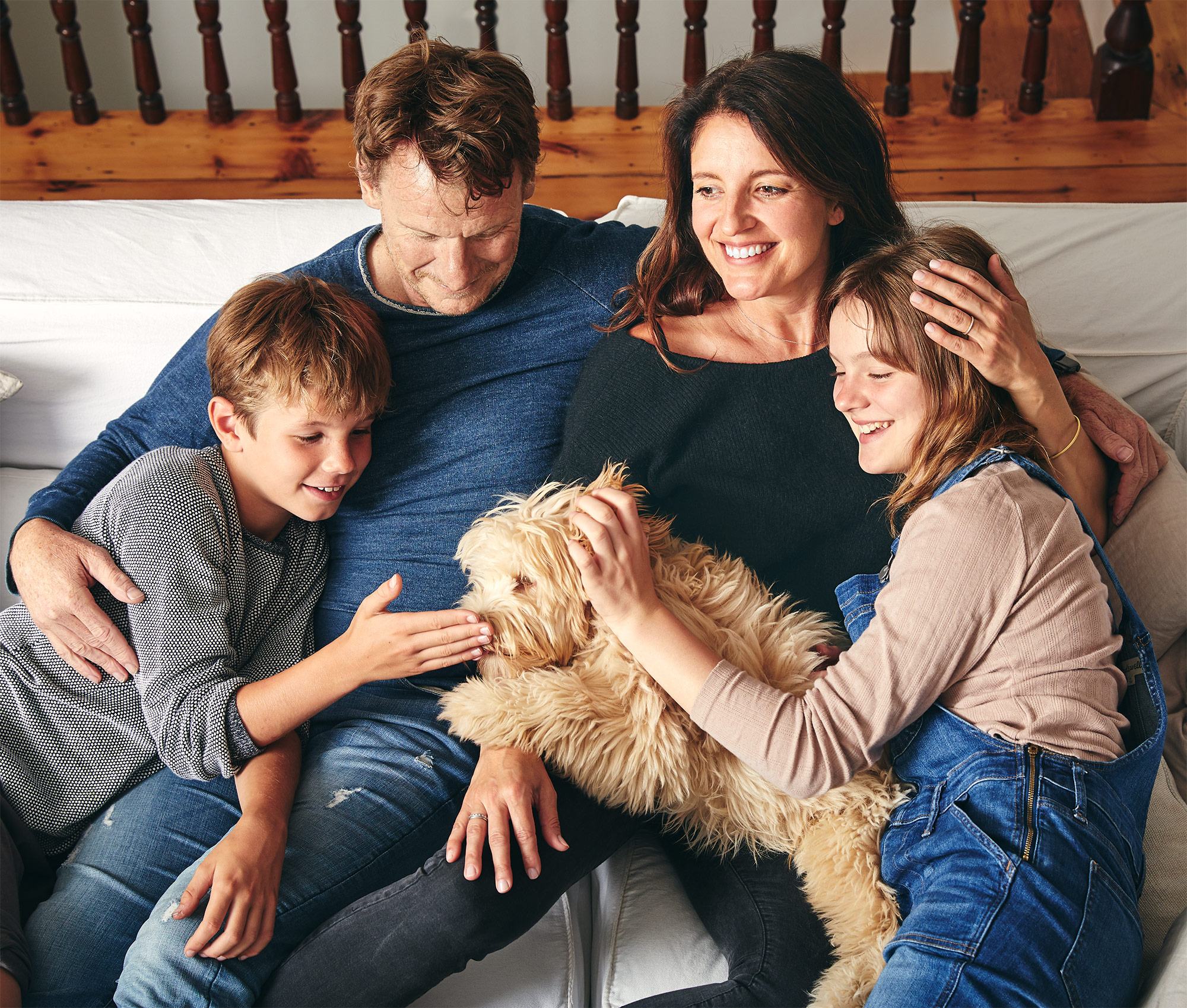 family on couch with dog