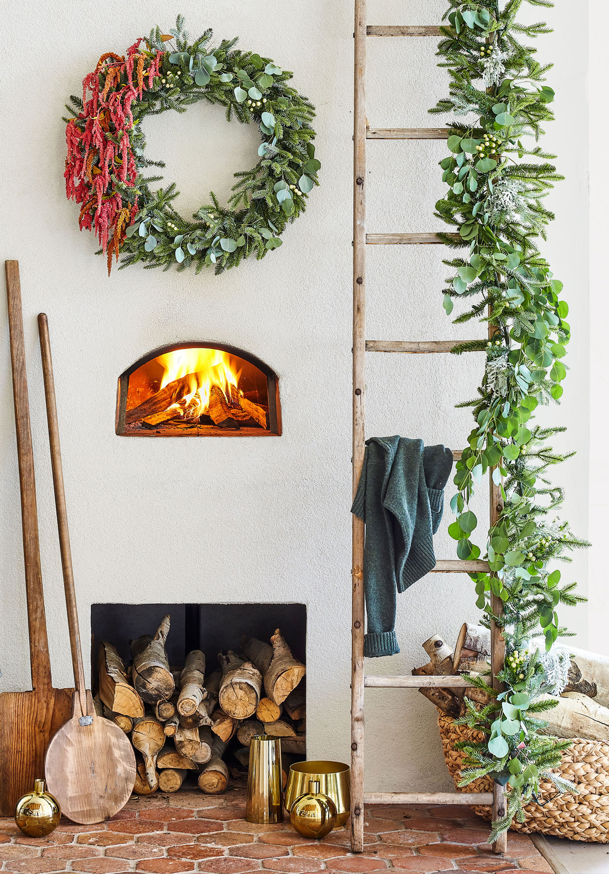 fireplace decorated with eucalyptus wreath and garland