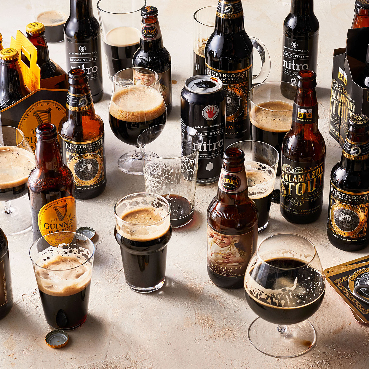 variety of stout bottles and cans among glasses