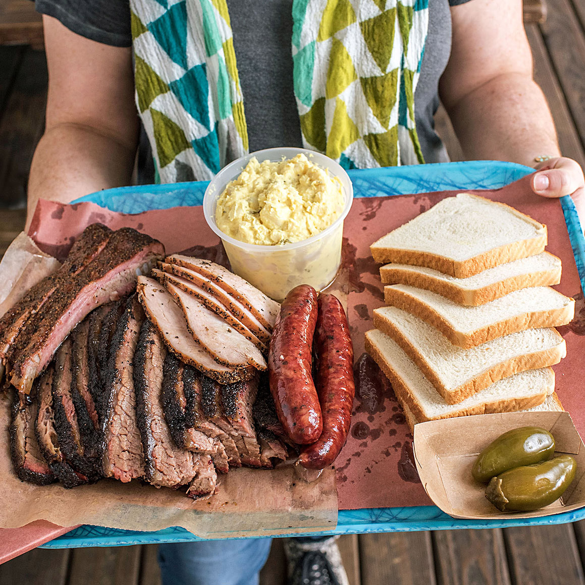 person holding tray of barbecue bread and potato salad