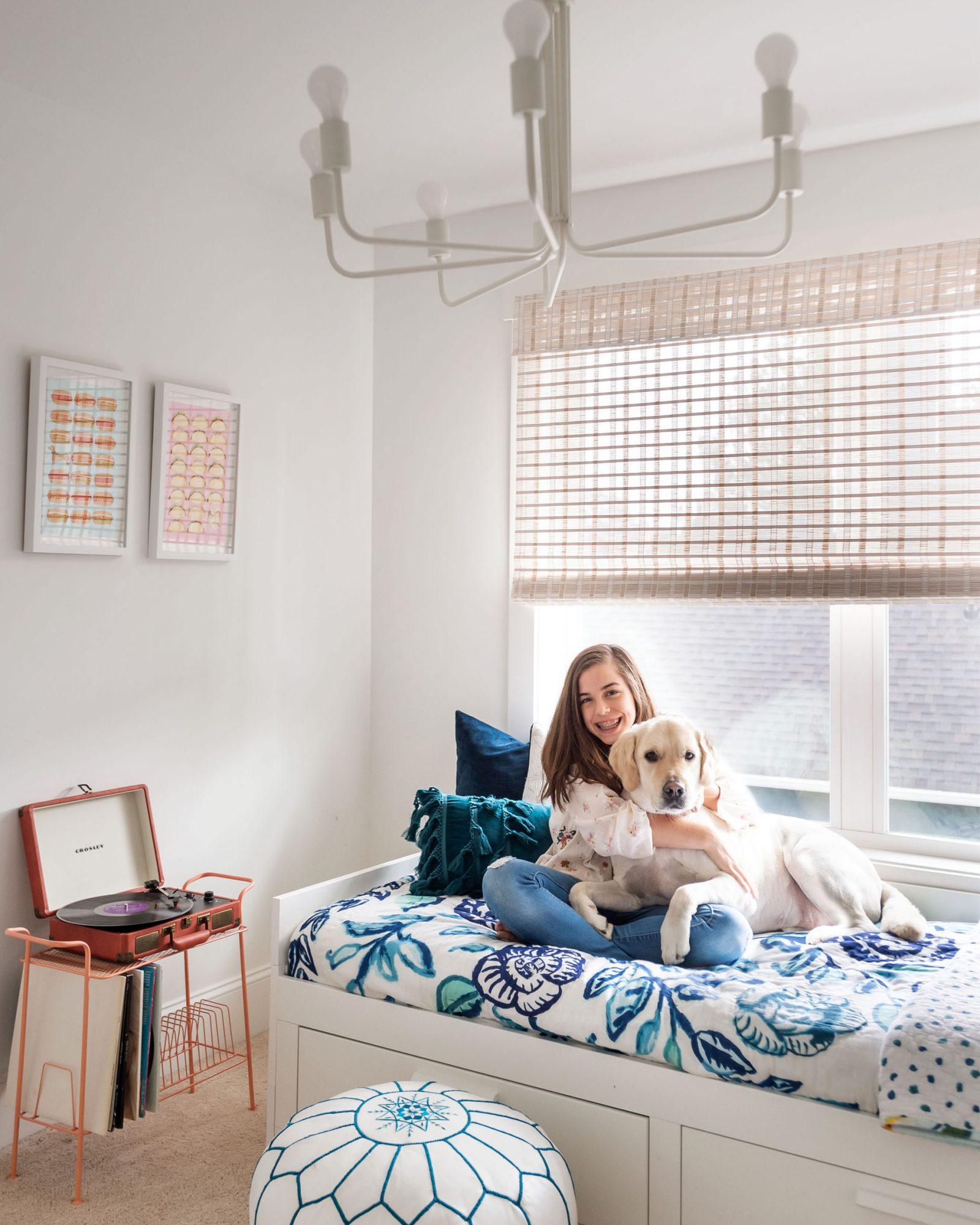 girl sitting on bed hugging dog