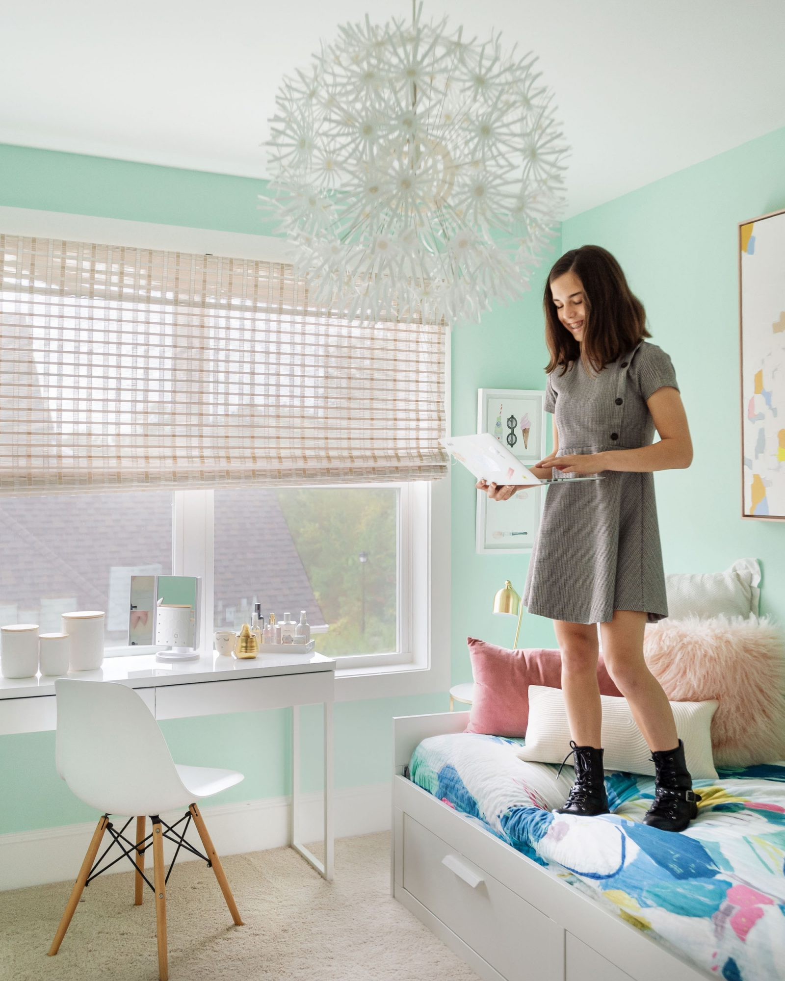 girl holding laptop standing on bed