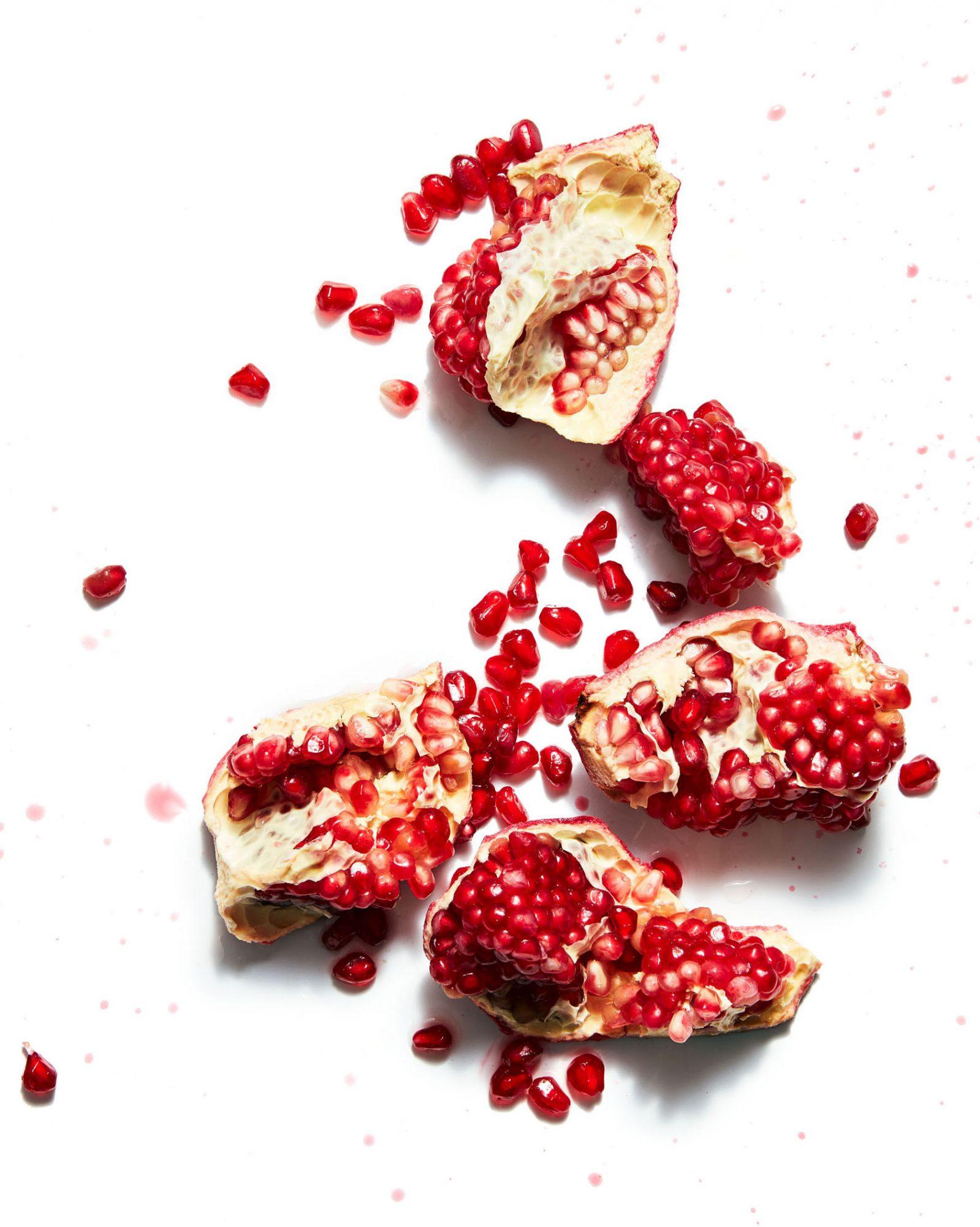 sliced pomegranate against white background
