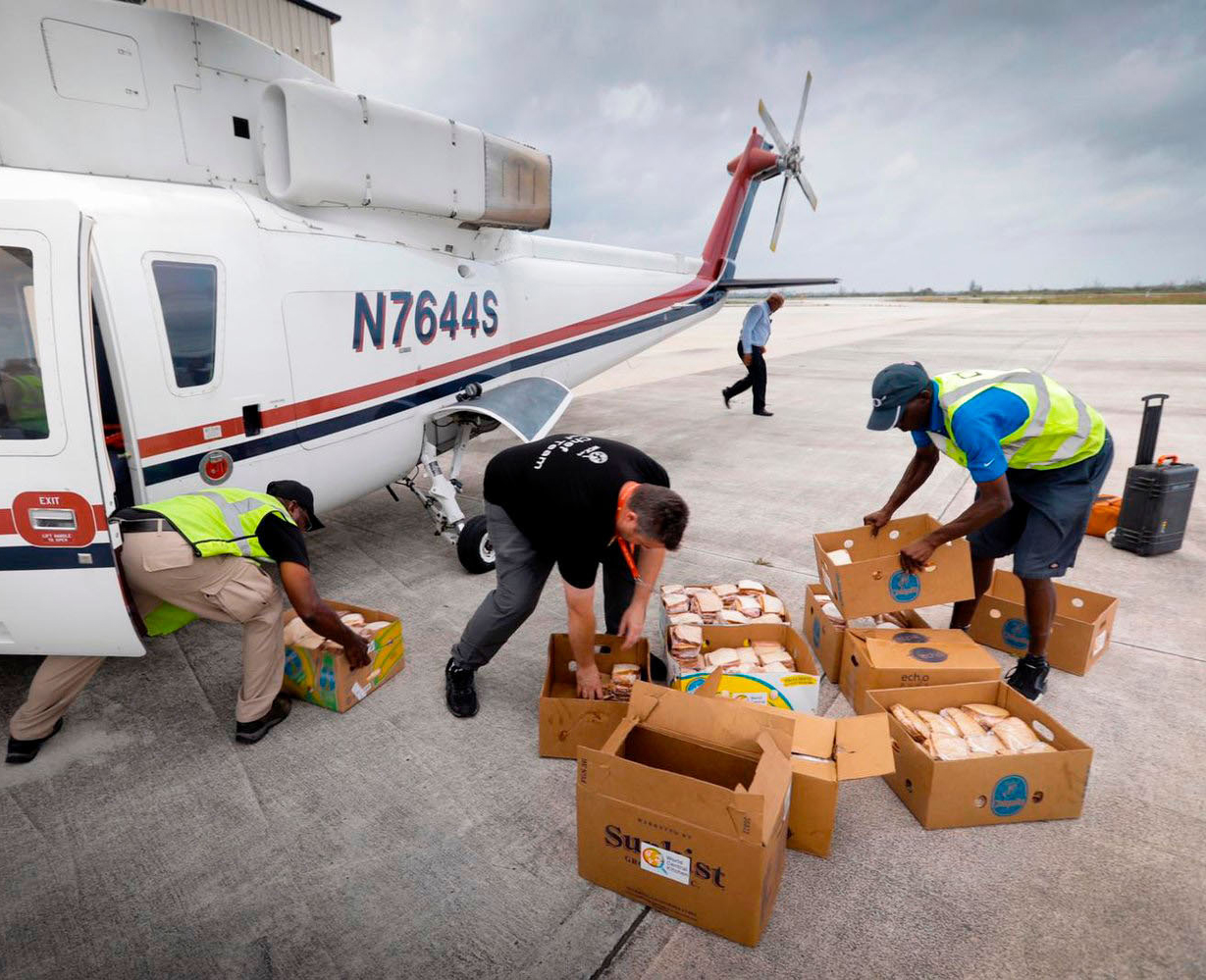individuals loading boxes of food onto plane