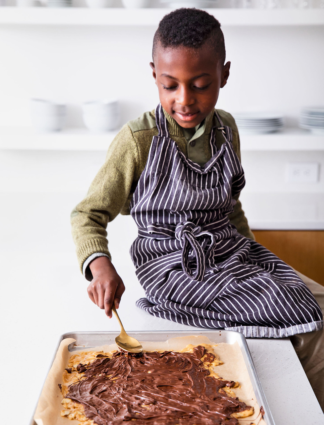 boy spreading chocolate on bark