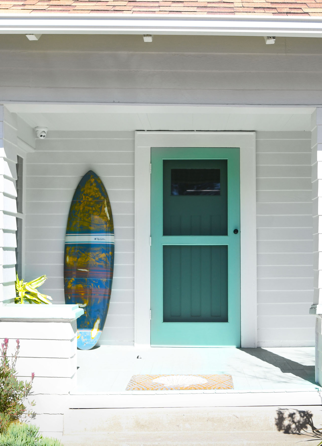 turquoise front door of white beach house