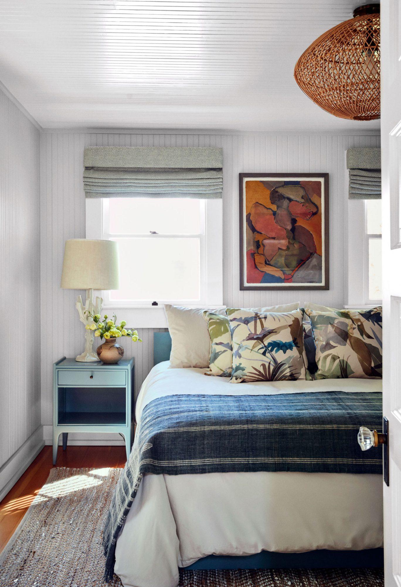 beachy master bedroom with vintage art